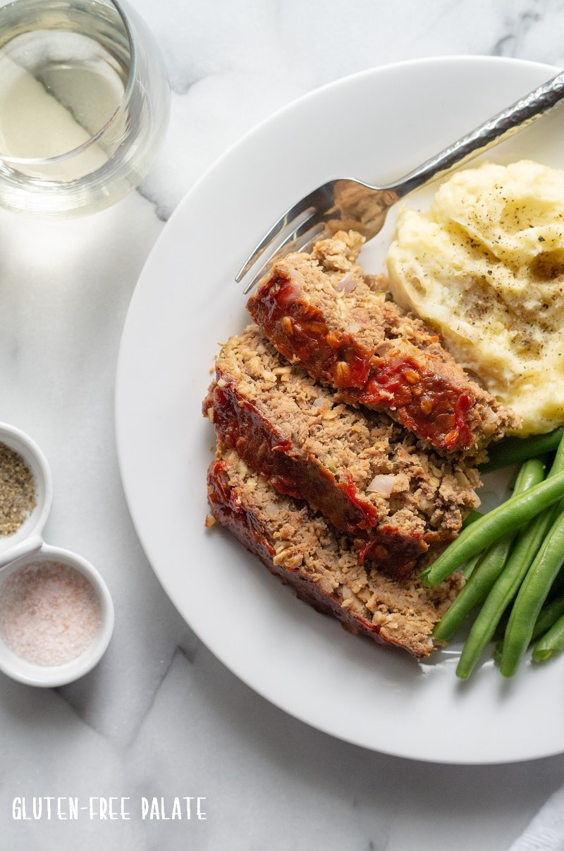 sliced Gluten-Free Meatloaf on a white plate with mashed potatoes and green beans