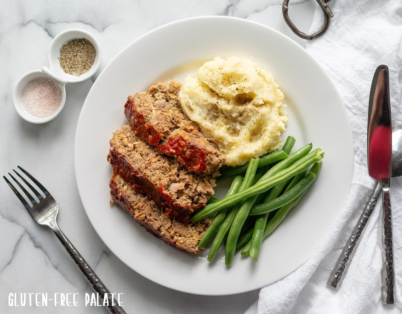 sliced Gluten-Free Meatloaf on a white plate with mashed potatoes and green beans, next to a fork and knife