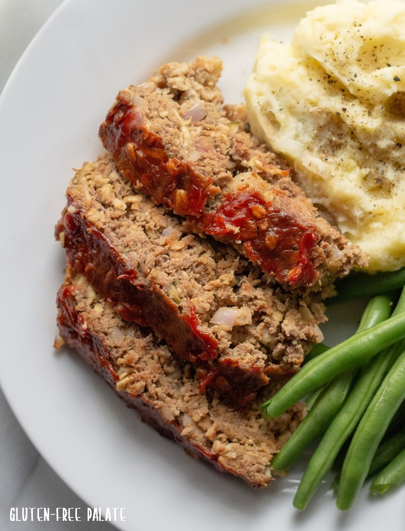 close up of sliced Gluten-Free Meatloaf on a white plate with mashed potatoes and green beans