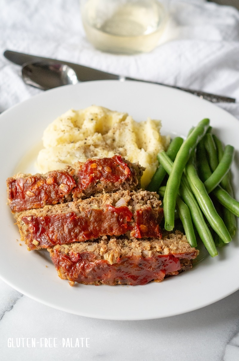 side view of sliced Gluten-Free Meatloaf on a white plate with mashed potatoes and green beans