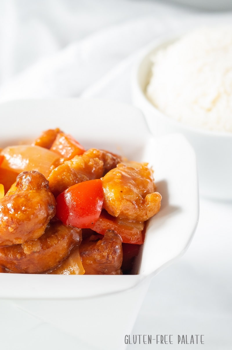 Gluten Free Sweet and Sour Chicken in a white dish with a bowl of rice in the background