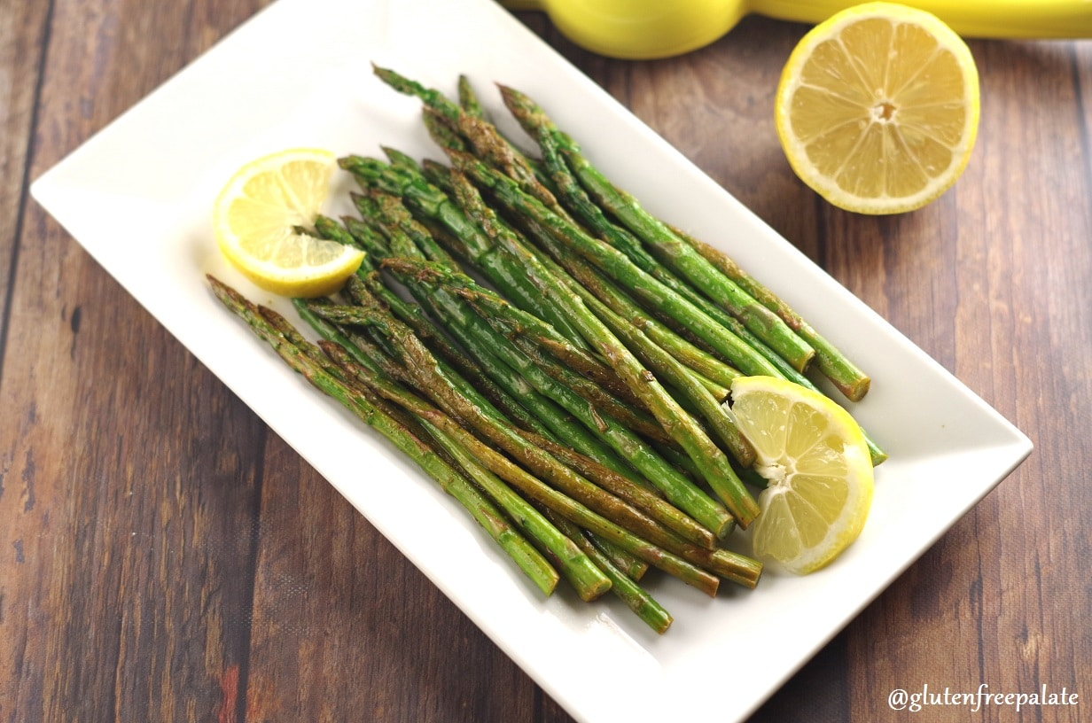 Asparagus spears on a white plate with slices of lemon