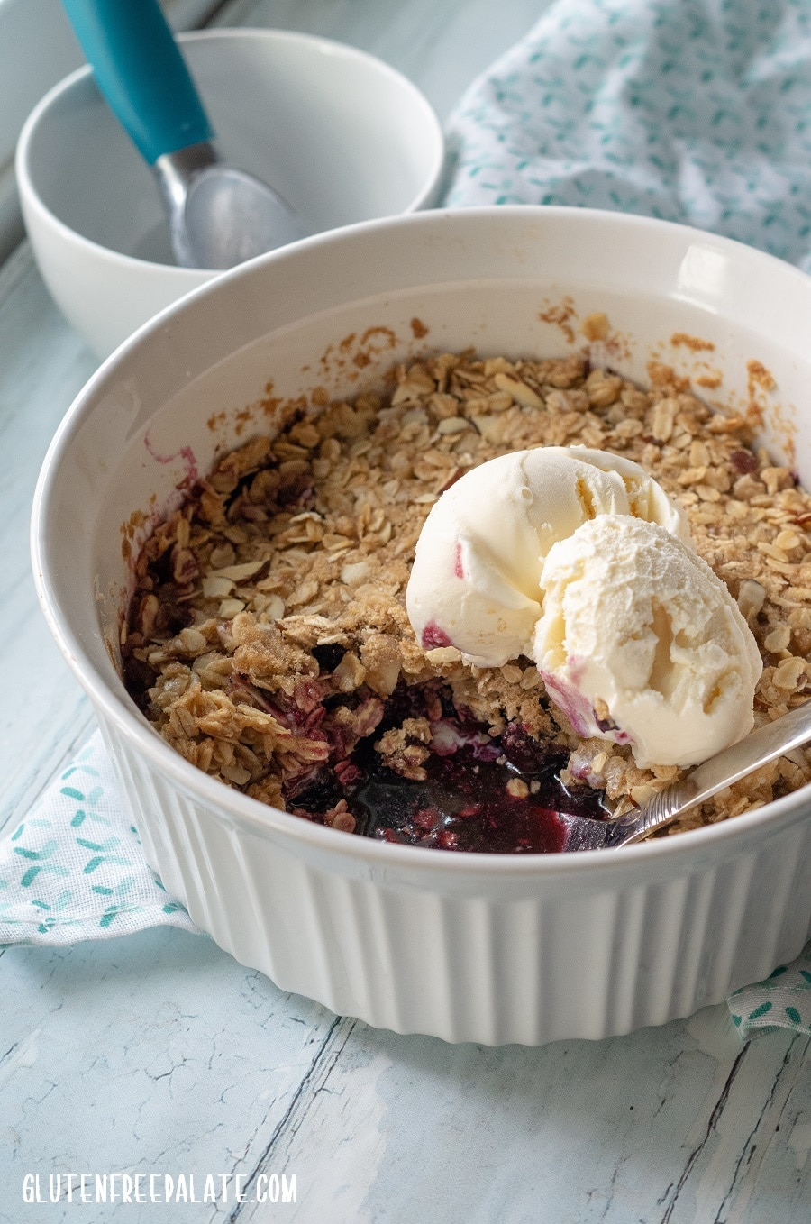 Gluten Free Blackberry crisp in a white dish with a spoon.