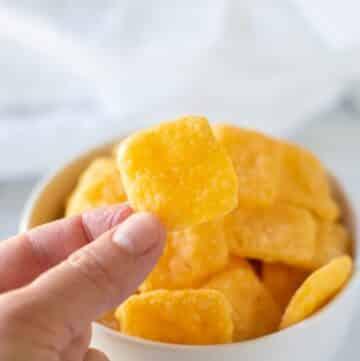 a hand holding a gluten free cheese cracker