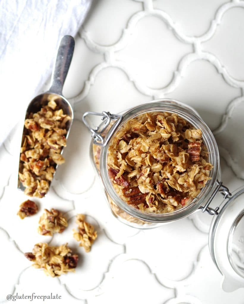 Gluten-Free Granola in a glass jar with a scoop.