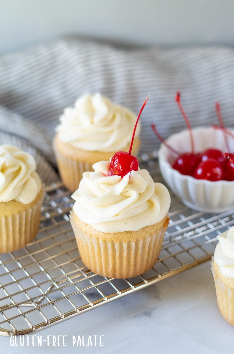 a white Gluten Free Root Beer Cupcake topped with white frosting with a cherry on top and a bowl of red cherries and additional cupcakes in the background