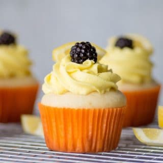 a close up of a lemon cupcake topped with yellow frosting and a blackberry, in a orange paper liner
