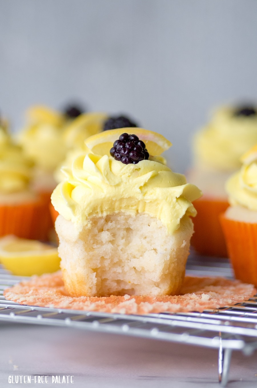 a lemon cupcake with yellow frosting and a blackberry on top, with a bite out