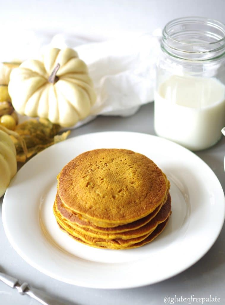 Gluten Free pumpkin pancakes stacked on a white plate.
