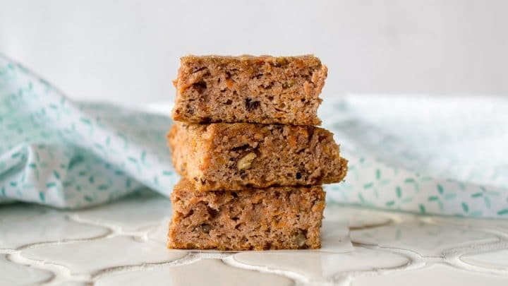 three Grain-Free Carrot Cake Bars stacked on a white counter