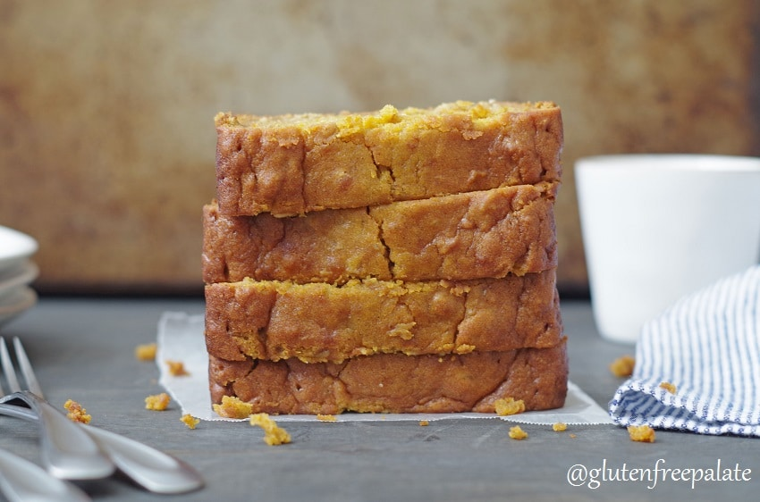 A loaf of gluten-free pumpkin bread stacked in slices on a white counter.