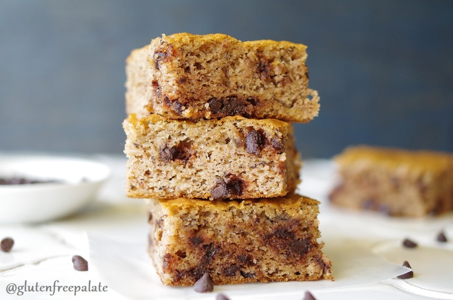 a close up of three paleo banana bars with chocolate chips stacked on a piece of parchment paper