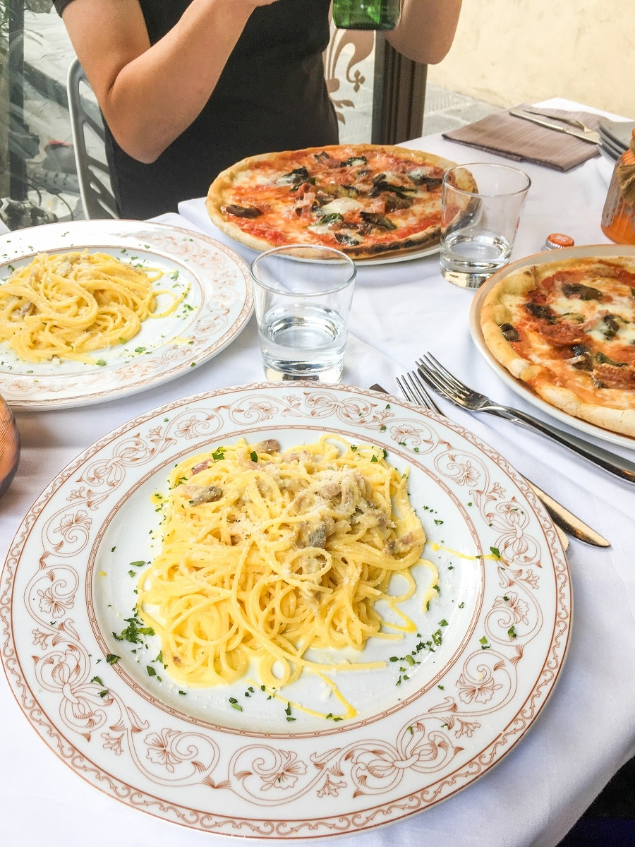a table with two plates of yellow pasta and two trays of round pizza with two glasses of water in the center