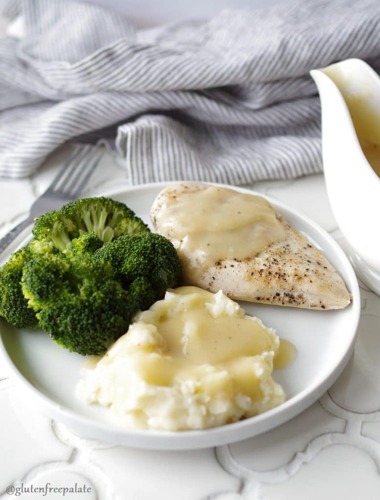chicken and mashed potatoes with gliten-free gravy on a white plate with broccoli next to a white gravy boat