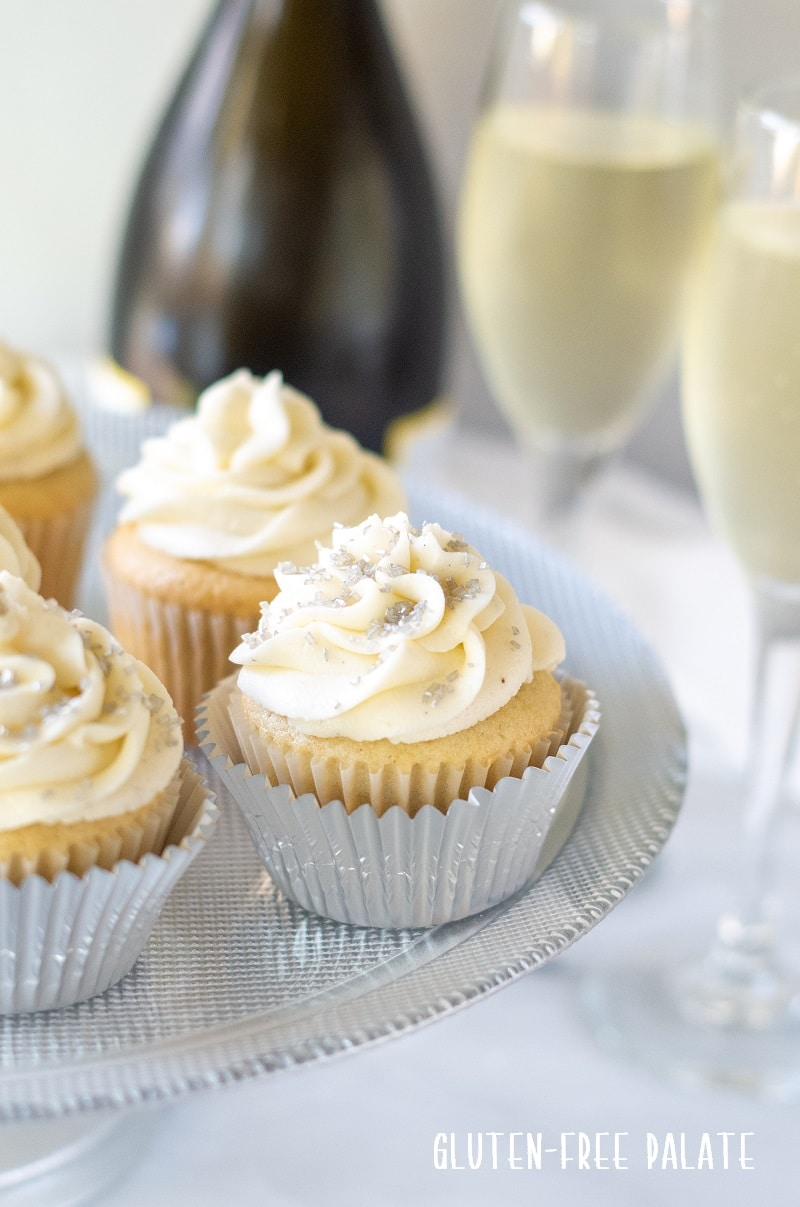 Gluten Free Champagne Cupcakes with champagne glasses in the background