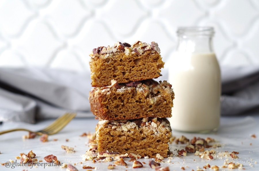 three slices of gingerbread cake stacked in front of a jar of milk next ot scattered nuts