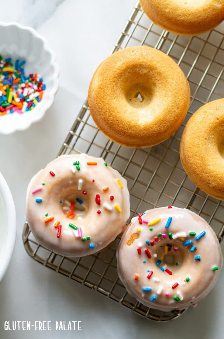 gluten free vanilla donuts with sprinkles on a wire cooling rack