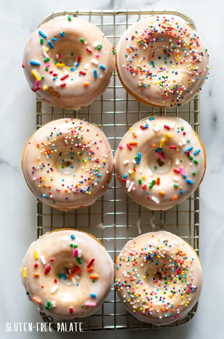 six gluten free donuts with glaze and sprinkles