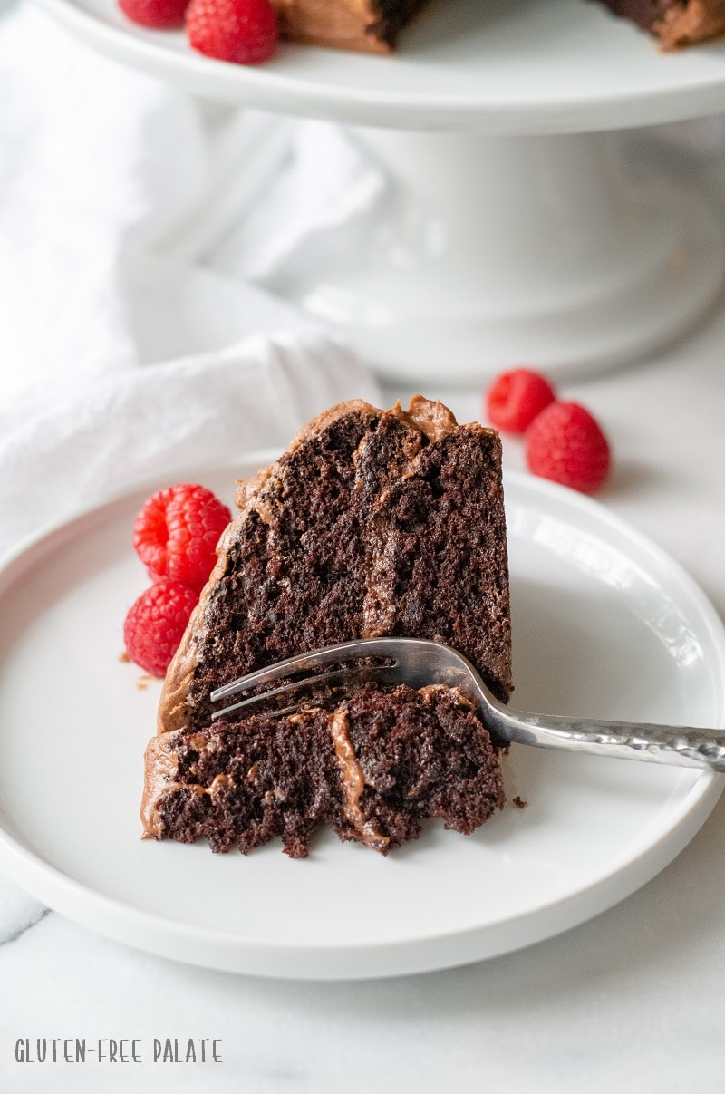 a slice of double layer chocolate cake with chocolate frosting and raspberries, with a fork taking a bite out