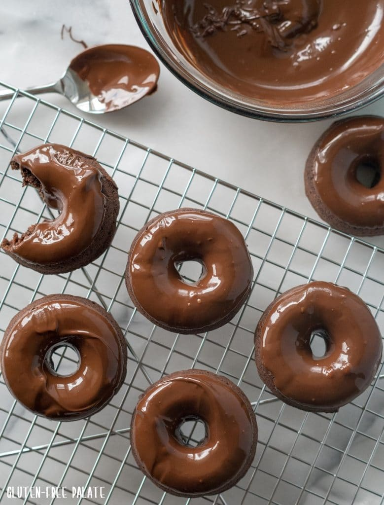 Gluten-Free Vegan Donuts with a chocolate glaze on a wire cooling rack next to a bowl of melted chocolate