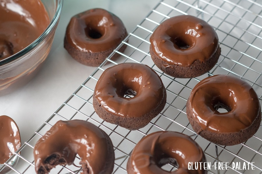 Gluten-Free Vegan Donuts with a chocolate glaze on a wire cooling rack, one has a bite taken out