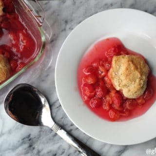 cherry cobbler on a white plate next to a serving spoon