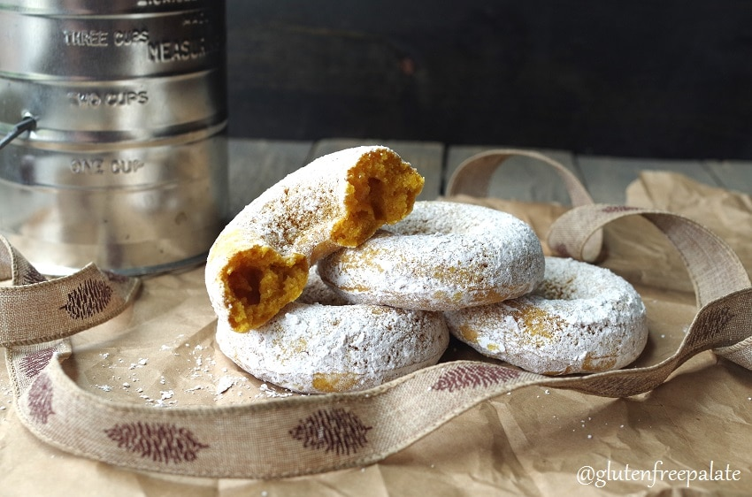 four gluten free pumpkin donuts arranged on a brown piece of paper, one donut is cut in half
