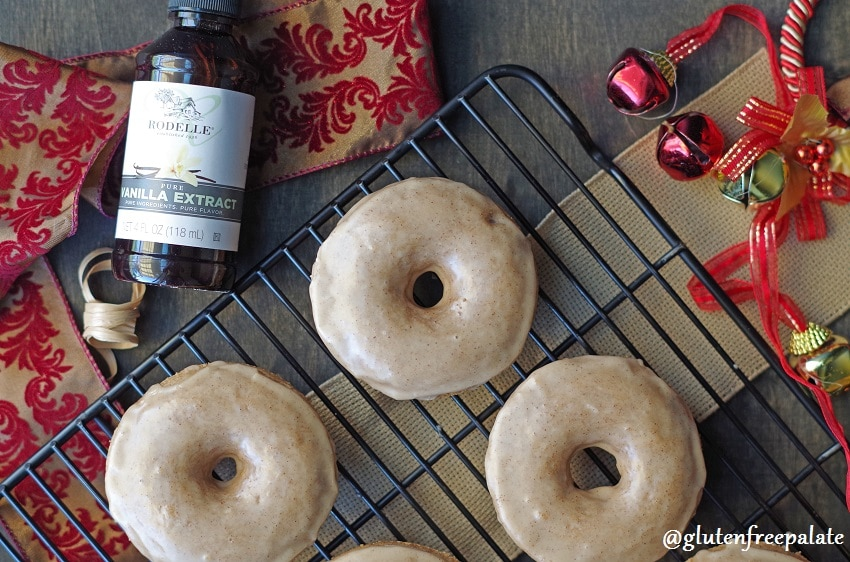 gluten free chai donuts on a wire rack next to a bottle of vanilla extract and a holiday ribbon