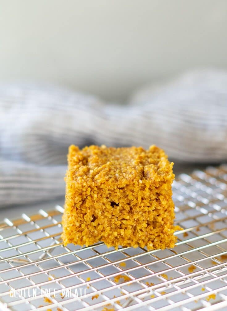 a close up of a slice of pumpkin cornbread on a cooling rack
