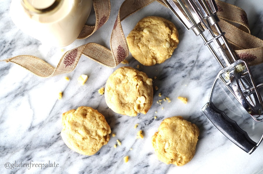 four gluten-free white chocolate macadamia cookies on a marble slab with a browni ribbon and hand beaters