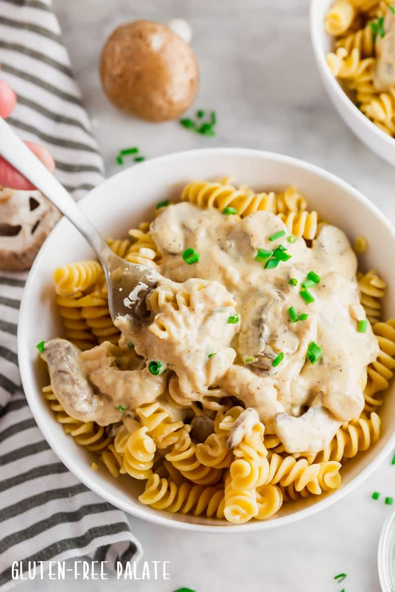 gluten free stroganoff sauce over noodles in a white bowl with a fork taking a bite out