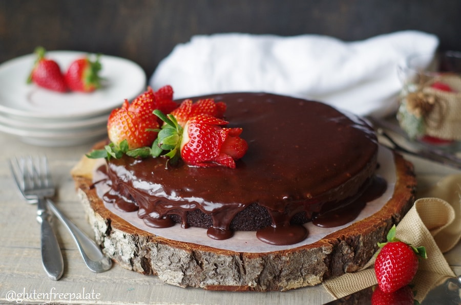 a Gluten-Free Vegan Chocolate Ganache Cake topped with strawberry roses, served on a wood cake platter