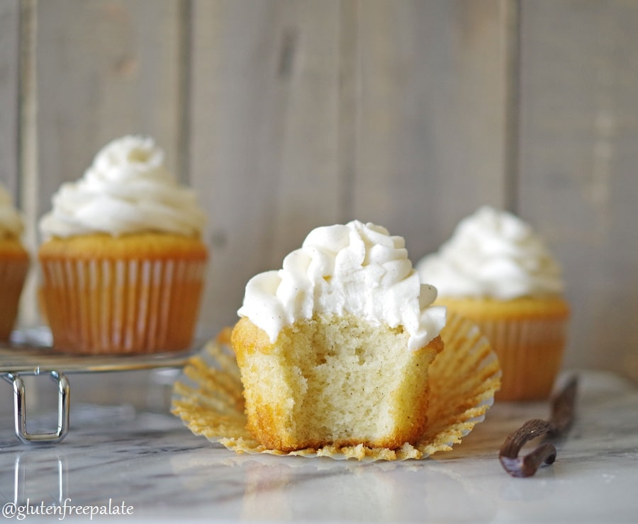 a gluten free vanilla cupcake topped with white frosting with a bite out