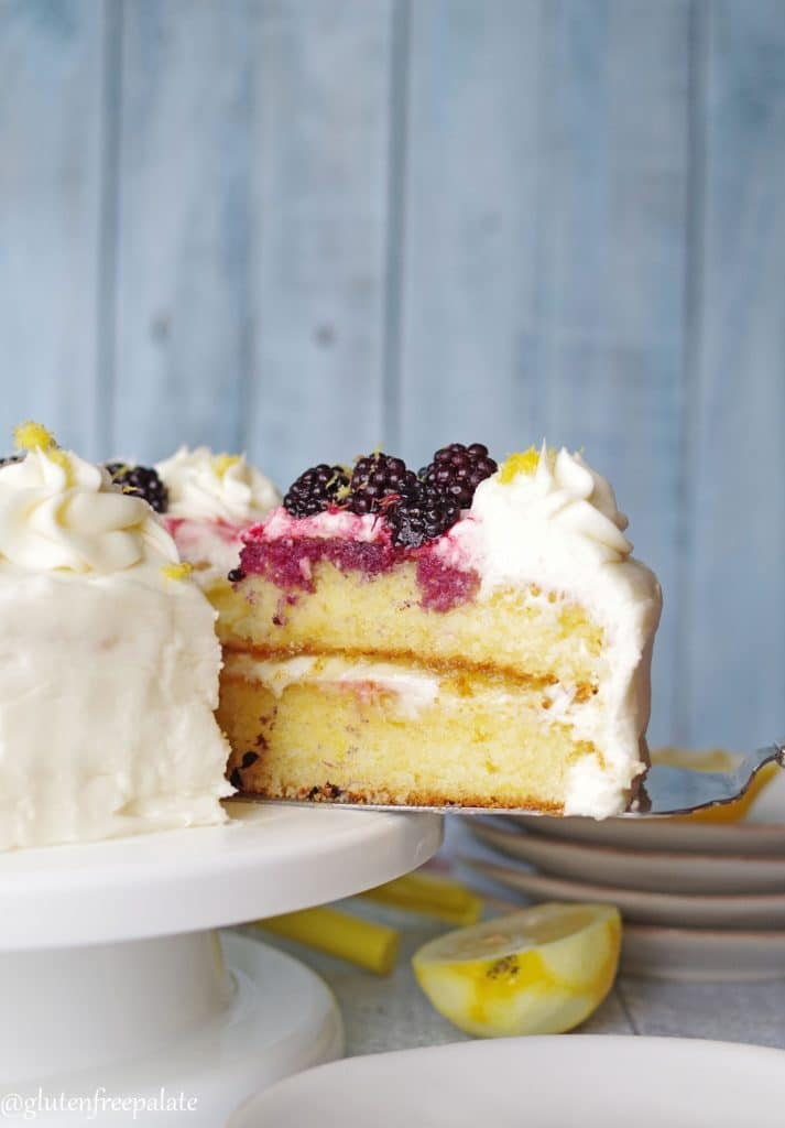 a serving spoon serving a slice of gluten-free lemon cake topped with white frosting and blackberries