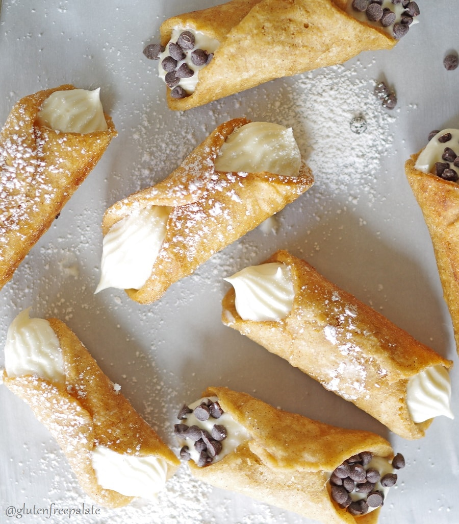 a close up of a top down view of cannolis dusted with powdered sugar