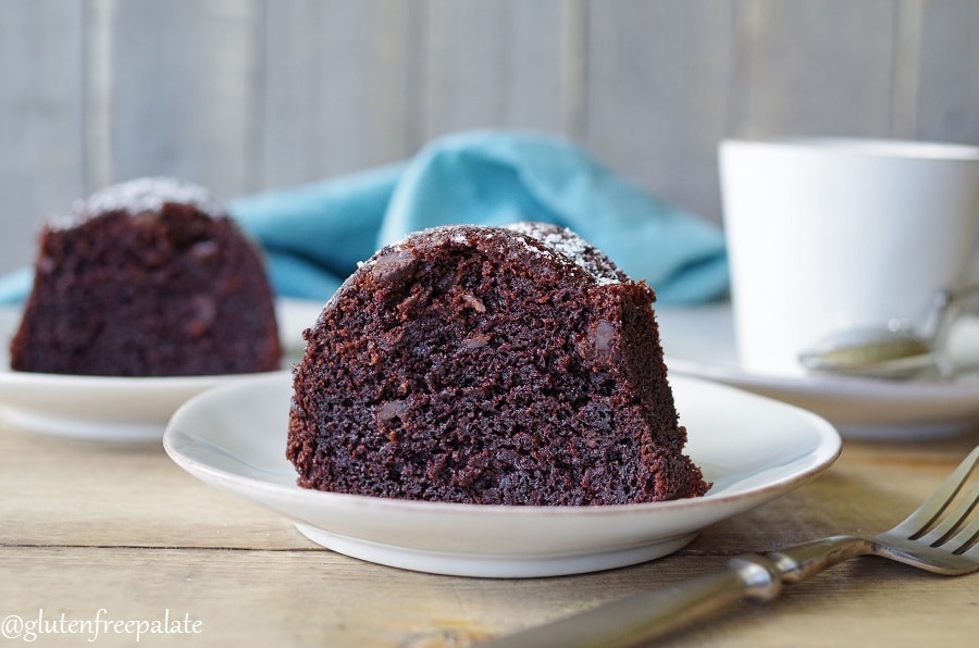 A slice of gluten-free chocolate bundt cake on a white plate.