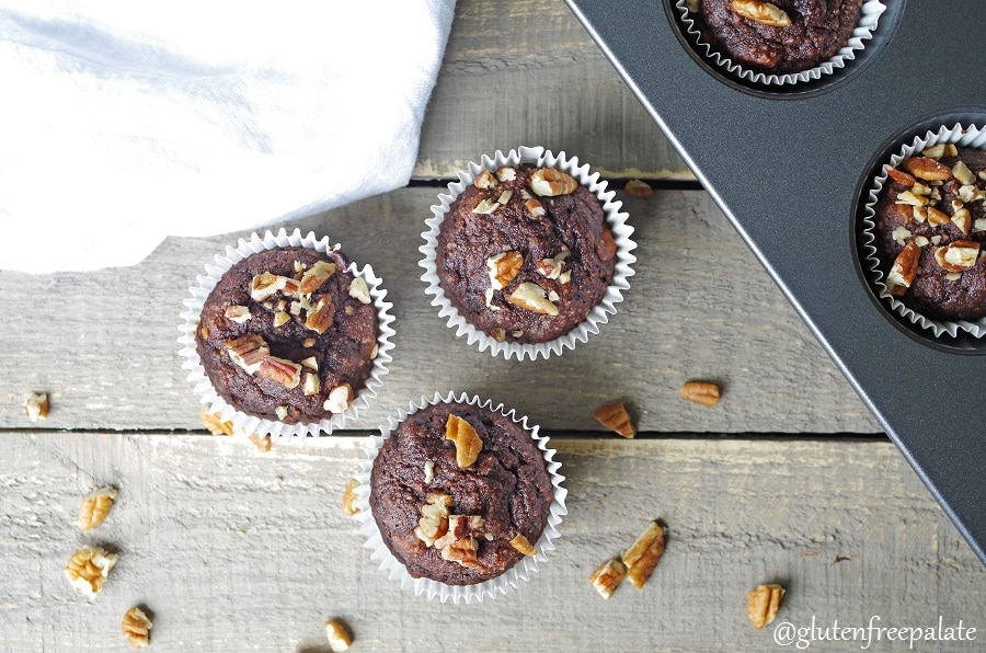 top down view of three chocolate banana muffins topped with chopped nuts, next to a pan of muffins