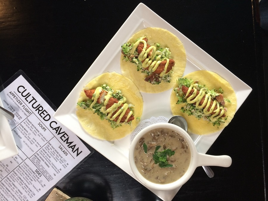 three fish tacos and a bowl of soup on a white plate