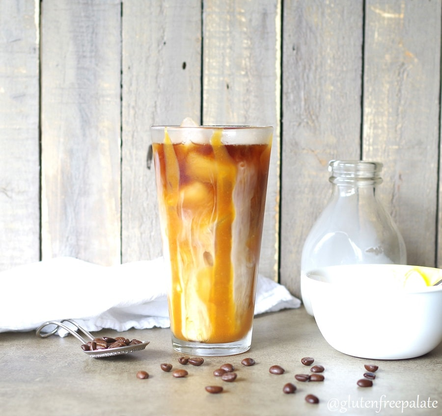 Homemade iced coffee in a glass with caramel and coffee beans