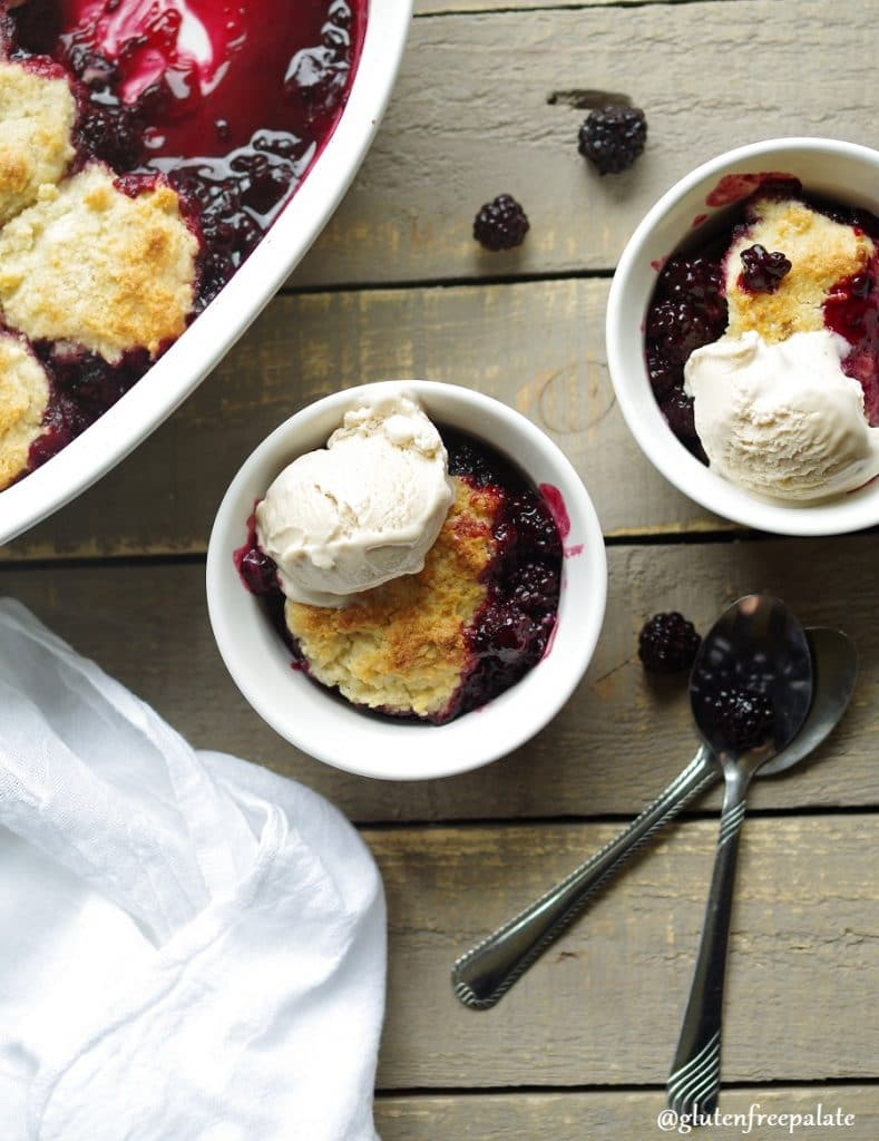 Gluten-Free Blackberry Cobbler in a white baking dish with vanilla ice cream.