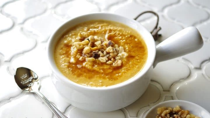 a side view of pumpkin porridge in a white bowl topped with chopped nuts, next to a spoon