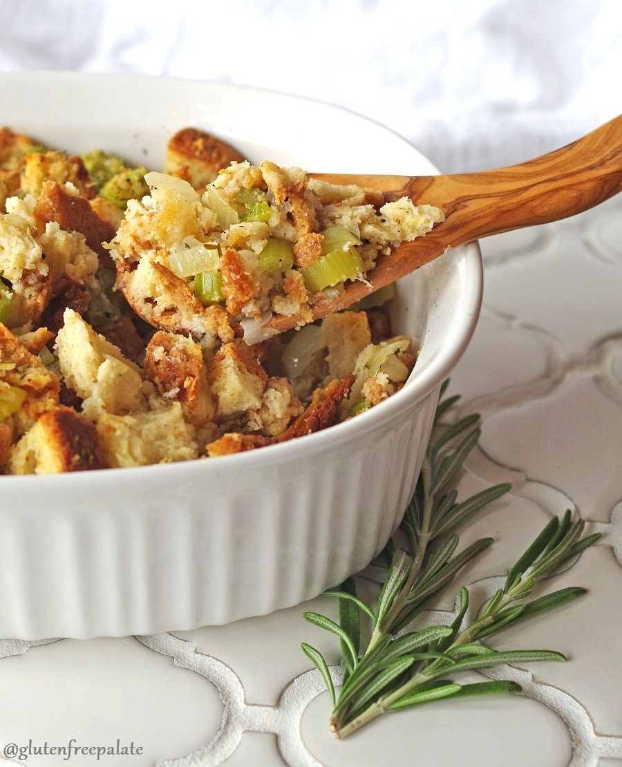 a white baking dish filled with gluten free stuffing cubes, celery and onion slices with a wooden spoon scooping stuffing out