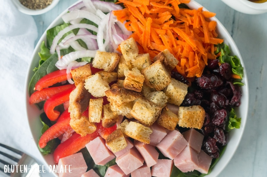 close up of a salad topped with croutons and veggies and ham