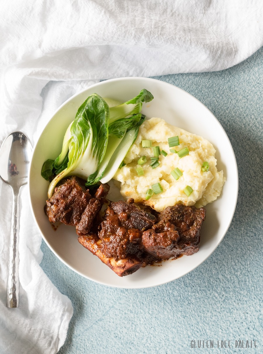 a close up of a top down view of beef short rib, mashed potatoes and green vegetables