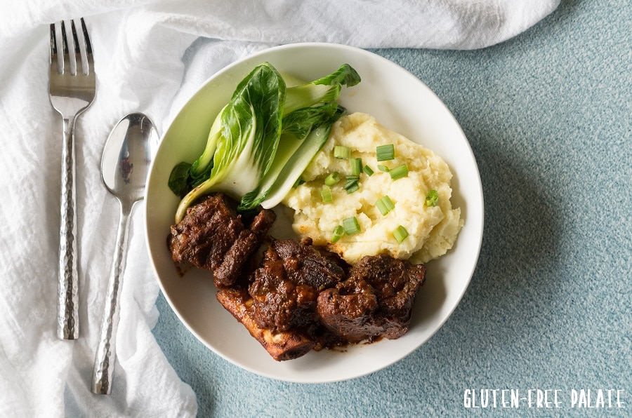 a top down view of beef short rib, mashed potatoes and green vegerables