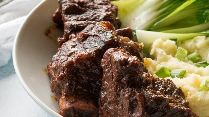side view of beef short rib, mashed potatoes and green vegetables on a white plate