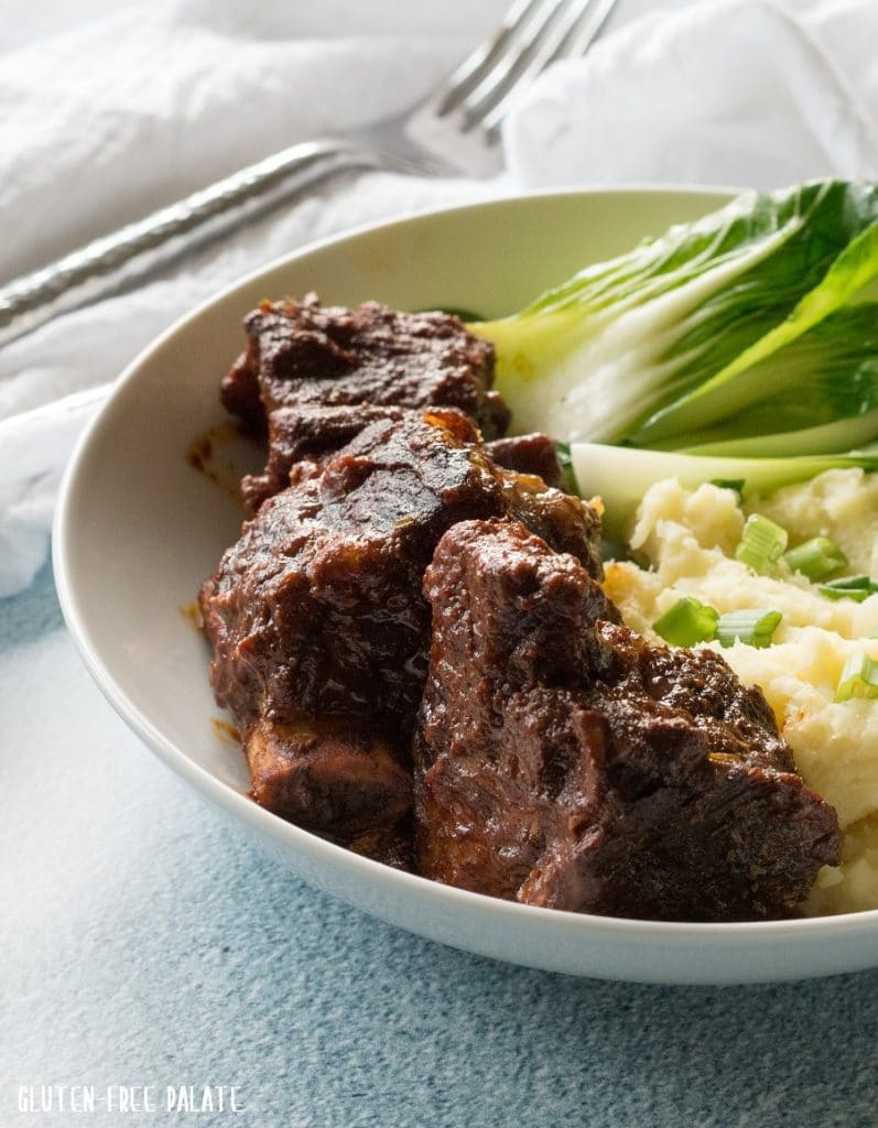 a side view of beef shortrib next to vegetables and mashed potatoes, on a white plate