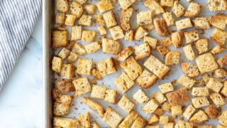 a top down view of cooked gluten free croutons on a baking sheet