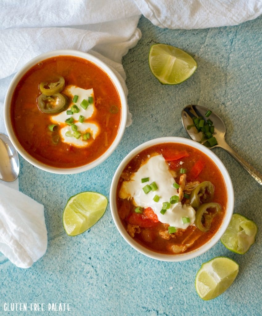 two bowls of chicken soup topped with sour cream and green onion next to lime wedges