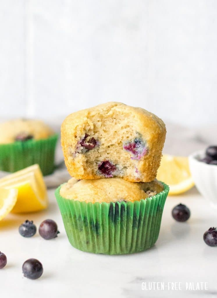 two paleo blueberry muffins stacked, the top muffin has a bite out showing the blueberries on the inside